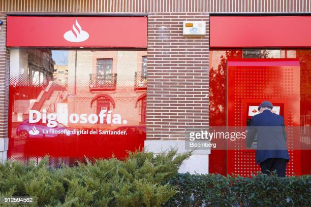A customer uses an automated teller machine outside a Banco Santander SA bank branch as Spain's largest lender reports fourth quarter earnings in...