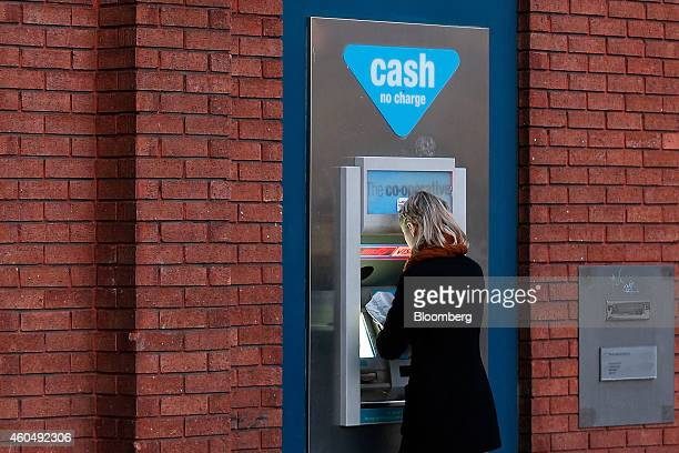 A customer uses an automated teller machine outside a CoOperative Bank Plc branch a unit of CoOperative Group Ltd in Manchester UK on Friday Dec 12...