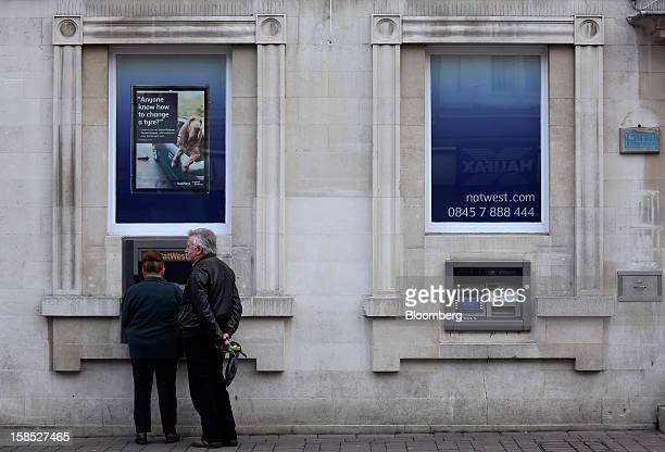 A customer uses an automated teller machine outside a NatWest bank branch part of the Royal Bank of Scotland Group Plc in Staines UK on Tuesday Dec...