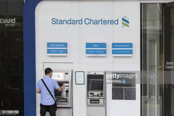 A customer uses an automated teller machine outside a Standard Chartered Plc bank branch in the central business district of Singapore on Monday Feb...