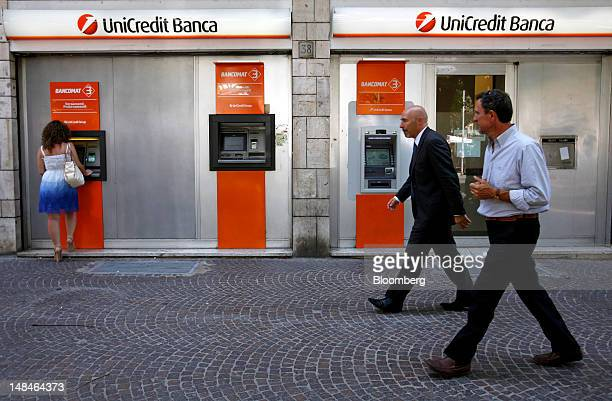 Customer uses an automated teller machine outside a UniCredit SpA bank branch in Rome, Italy, on Tuesday, July 17, 2012. UniCredit SpA and Intesa...