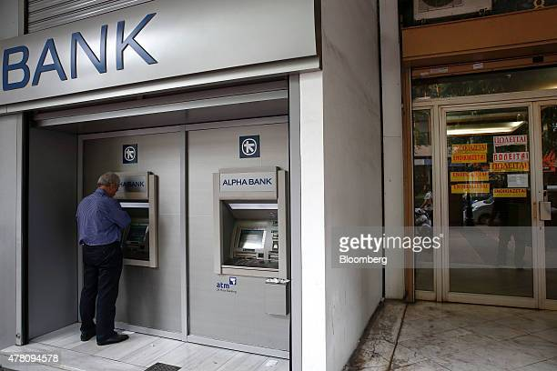 A customer uses an automated teller machine outside an Alpha Bank AE bank branch in Athens Greece on Monday June 22 2015 Dutch Finance Minister...