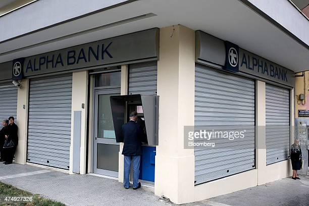 A customer uses an automated teller machine while pensioners wait to collect their pension payments outside a closed Alpha Bank AE bank branch in...