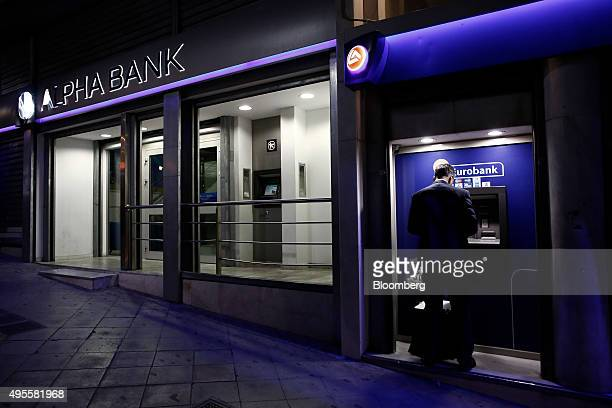 A customer uses an automated teller machines operated by Eurobank Ergasias SA beside an Alpha Bank AE bank branch in Athens Greece on Tuesday Nov 3...