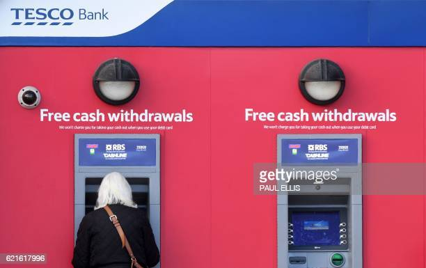 A customer uses an RBS branded automated teller machine at a Tesco Bank cash point in Liverpool north west England on November 7 2016 Britain's Tesco...