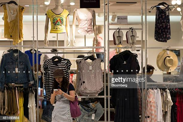A customer uses her mobile phone in front of clothing displays at the I'Park Mall department store majorityowned by Hyundai Development Co in Seoul...