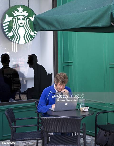 A customer uses his Apple computer while sitting outside a Starbucks coffee shop on the Strip in Las Vegas Nevada