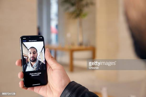 A customer uses the new facerecognition software on the Apple iPhone X the new model of Apple smartphone at the Apple Store SaintGermain on November...