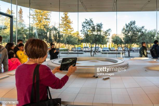 A customer using an iPad for an augmented reality tour to see a virtual version of the Apple Park campus at the Apple Park Visitor Center in Cupertino
