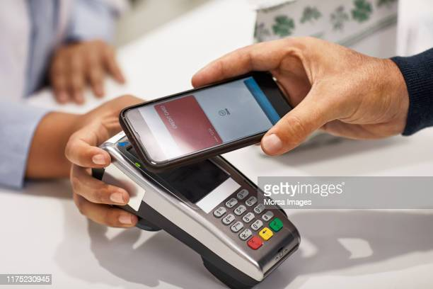 customer using contactless payment at pharmacy - paying stock pictures, royalty-free photos & images