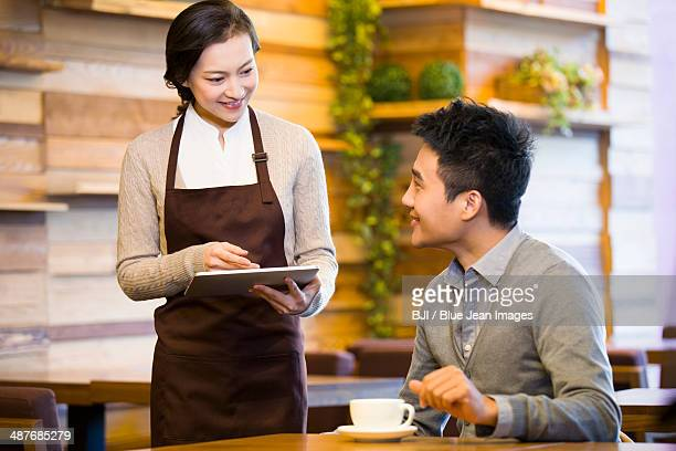 Customer using digital tablet for ordering