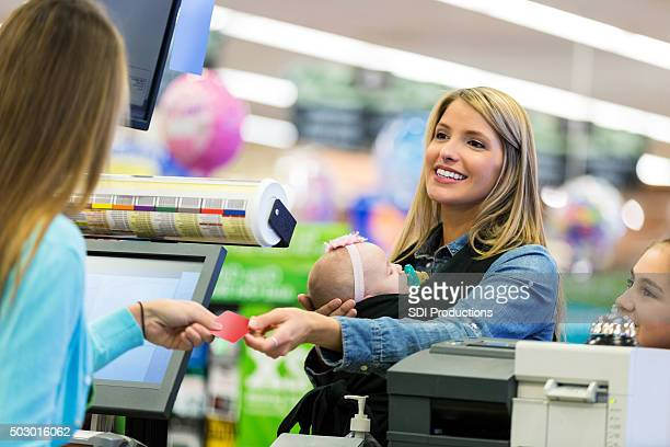 Customer using loyalty card or credit card at supermarket