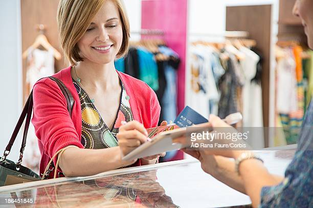 Customer using tablet pc to pay for shopping in boutique