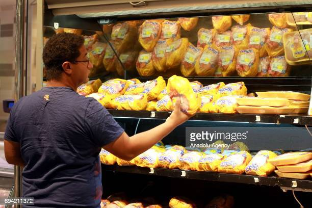 A customer views a chicken at Al Meera market in Doha Qatar on June 9 2017 People only rushed to markets and stocked food until the shelves were...