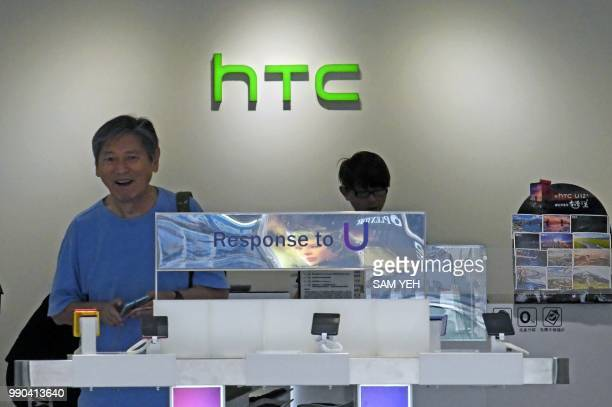 A customer visits a shop for Taiwan smartphone maker HTC in Taipei on July 3 2018 Taiwan's struggling smartphone maker HTC announced on July 3 it...