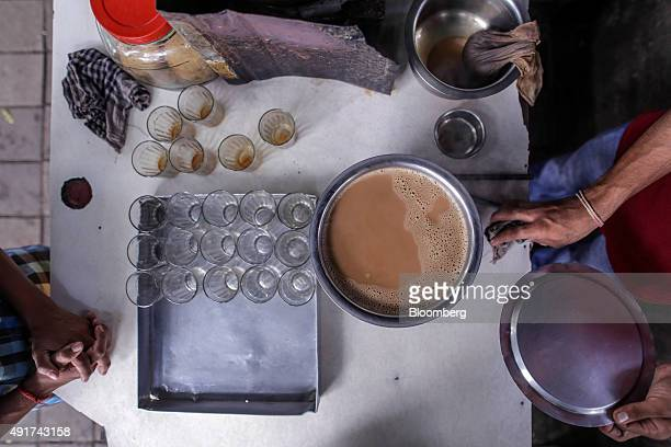 A customer waits as a vendor prepares chai at a stall in Mumbai India on Friday Sept 25 2015 That sweet and milky tea concoction called chai is...