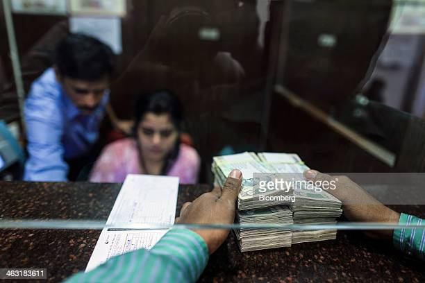 A customer waits to deposit Indian 1000 rupee banknotes at a counter inside an Axis Bank Ltd branch in Mumbai India on Thursday Jan 16 2014 Axis Bank...