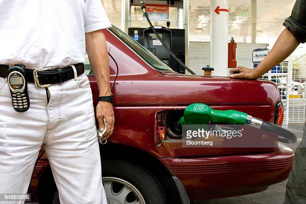 A customer waits while his car is filled at a Pemex gas station in Mexico City Mexico on Wednesday June 25 2008 Mexicans are coping with Mexico's...