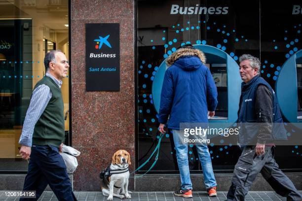 A customer walking a dog uses an automated teller machine outside a CaixaBank SA bank branch in Barcelona Spain on Thursday March 5 2020 Spanish bank...