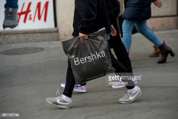 A customer walking carries a Bershka shopping bag on the first day of the winter sales in Barcelona on January 7 2017 / AFP PHOTO / Josep LAGO