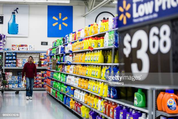 A customer walks down an aisle displaying bottles of laundry detergent for sale at a Walmart Inc store in Secaucus New Jersey US on Wednesday May 16...