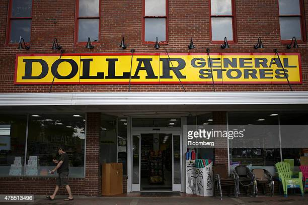 A customer walks down the sidewalk after shopping at a Dollar General Corp store in Scottsville Kentucky US on Tuesday May 26 2015 Dollar General...