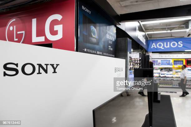 A customer walks near Sony and LG OLED televisions at the Bic Camera Yurakucho electronics store on June 5 2018 in Tokyo Japan The store is one of...