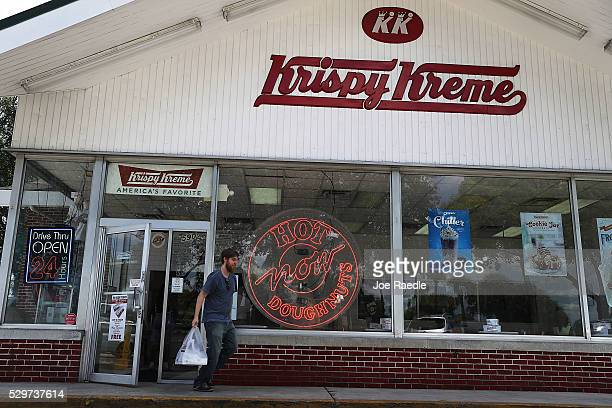Customer walks out of a Krispy Kreme donut shop on May 09, 2016 in Miami, Florida. JAB Holdings Company, announced it is acquiring Krispy Kreme...