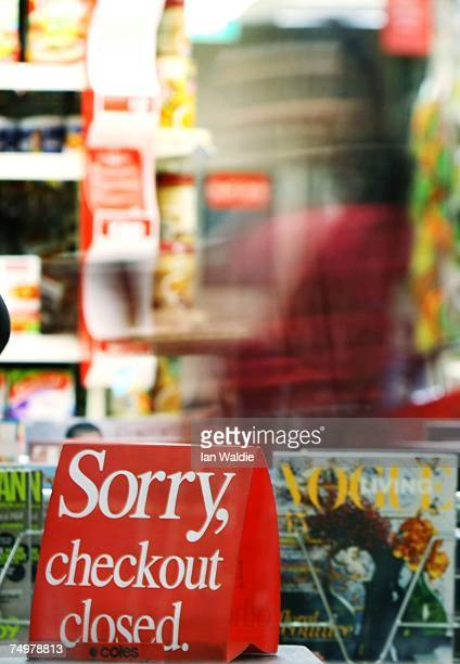 A customer walks past a closed checkout in a Coles supermarket after the announcement of Wesfarmers takeover bid July 2 2007 in Sydney Australia The...