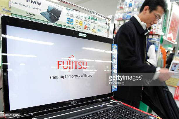 A customer walks past a Fujitsu Ltd FMV laptop computer displaying the company's logo on its screen at the Labi Ofuna electronics store operated by...