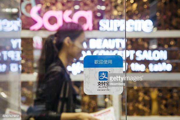 A customer walks past a sign for Ant Financial Services Group's Alipay an affiliate of Alibaba Group Holding Ltd at a Sa Sa International Holdings...