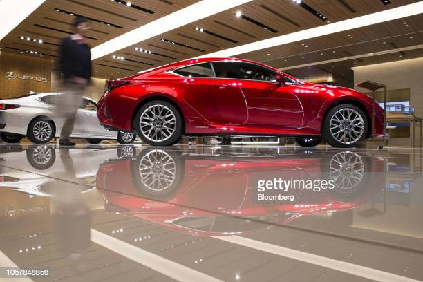 A customer walks past a Toyota Motor Corp Lexus RC300h coupe left and an ES300h sedan on display at the Lexus Meets Hibiya showroom in Tokyo Japan on...