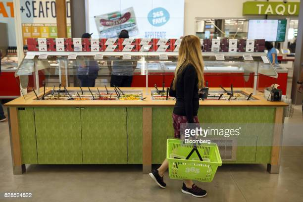 A customer walks past an olive bar during the grand opening of a Whole Foods Market 365 location in Santa Monica California US on Wednesday Aug 9...