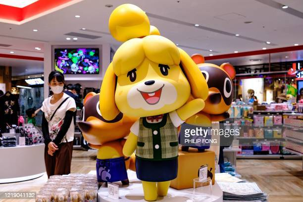 Customer walks past Animal Crossing video game characters at a Nintendo store in Tokyo on June 10, 2020.