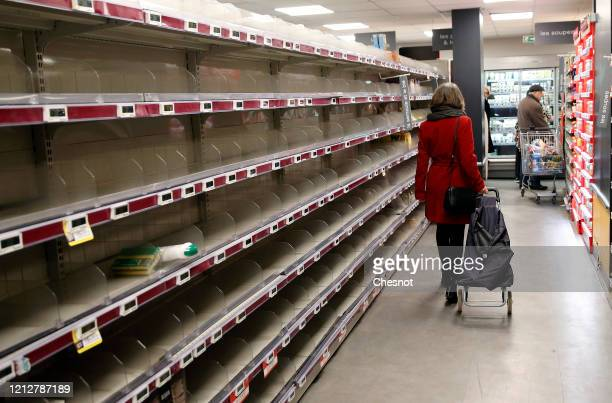 A customer walks past nearly empty shelves at a Monoprix supermarket as people began stockpiling food in Paris due to an outbreak of coronavirus...