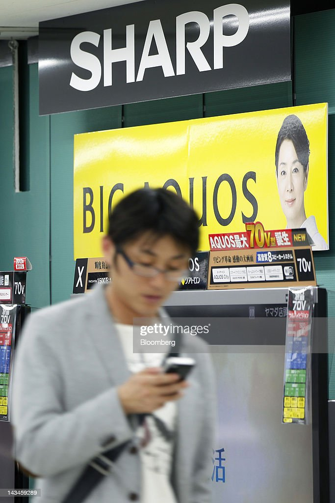 A customer walks past Sharp Corp. Aquos liquid crystal display (LCD) televisions at the Labi Ofuna electronics store, operated by Yamada Denki Co., in Yokohama City, Kanagawa Prefecture, Japan, on Friday, April 27, 2012. Sharp Corp., Japan's biggest maker of LCD panels, forecast a net loss wider than analyst estimates as falling TV prices prompted the company to turn to Foxconn Technology Group for investment. Photographer: Kiyoshi Ota/Bloomberg via Getty Images