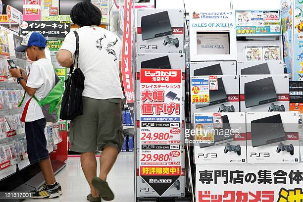 A customer walks past Sony Computer Entertainment Inc's PlayStation 3 video game consoles displayed for sale as a boy tries out a Nintendo Co 3DS...