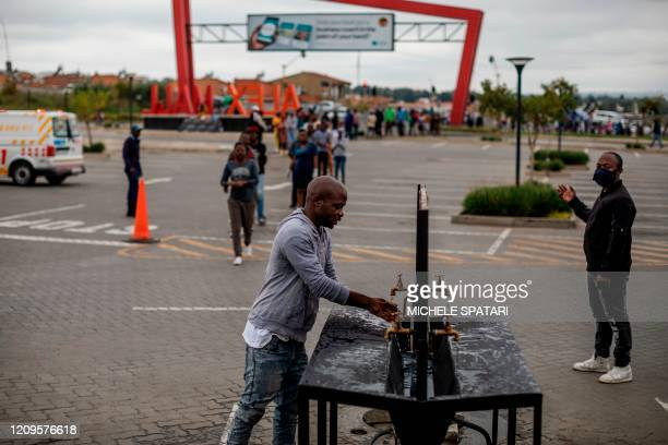 Customer washes his hands after queuing at the entrance of a shopping mall in Alexandra, Johannesburg, on April 10, 2020. - Alexandra township local...