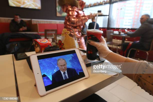 Customer watches a live broadcast of Vladimir Putin, Russia's President, delivering his annual news conference, on an Apple Inc. IPad inside a Burger...