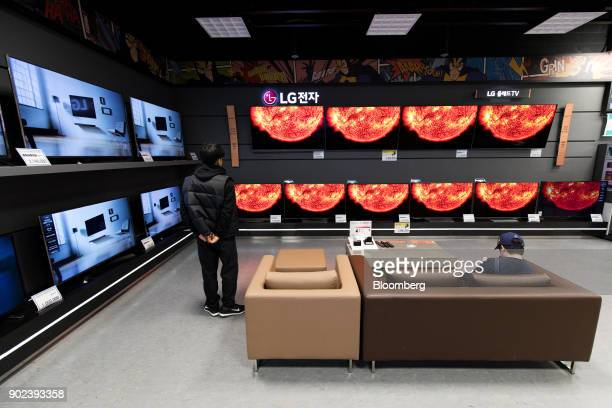 A customer watches LG Electronics Inc curved organic lightemitting diode televisions at an EMart Inc Electro Mart store in Gimpo South Korea on...