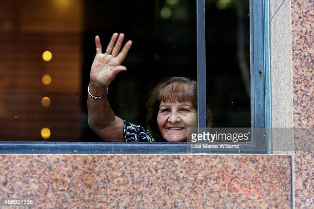 A customer waves and smiles to the awaiting crowd from a window at the Lindt Cafe in Martin Place on March 20 2015 in Sydney Australia The cafe...