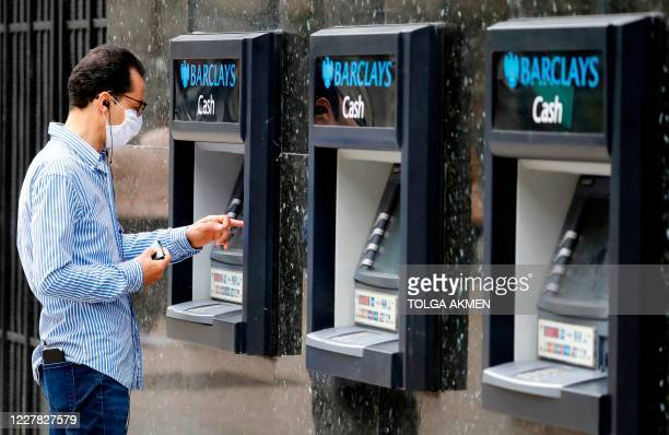 A customer wearing a face mask or covering due to the COVID19 pandemic uses an ATM machine outside a branch of a Barclays bank in central London on...