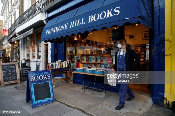 Customer wearing a face mask or covering due to the COVID-19 pandemic, leaves from Primrose Hill Books, an independent book shop in west London on...