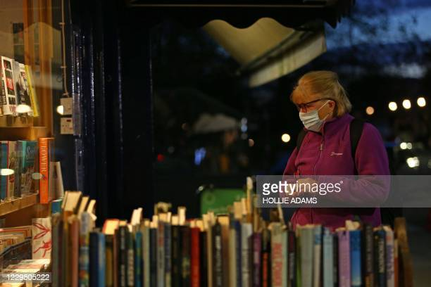 Customer wearing a face mask or covering due to the COVID-19 pandemic, browses books displayed outside Primrose Hill Books, an independent book shop...