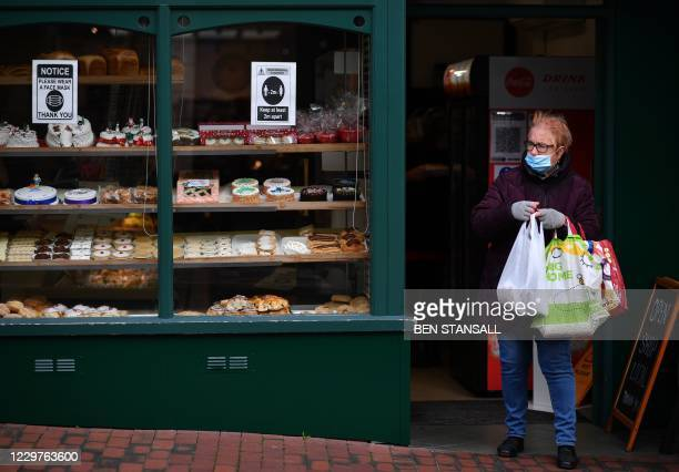 Customer wearing a face mask or covering due to the COVID-19 pandemic, carries her shoppingas she leaves a patisserie in Sittingbourne in the Swale...