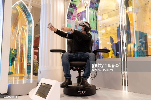 Customer wearing a face mask or covering due to the COVID-19 pandemic, trials wearable VR electronics inside the Selfridges department store as it...