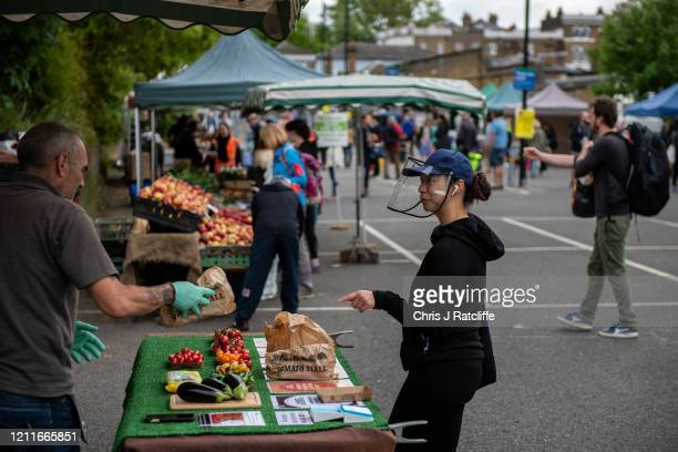 A customer wearing a face shield buys tomatoes from a stall at Blackheath Farmers Market on May 3 2020 in London England The Office For National...