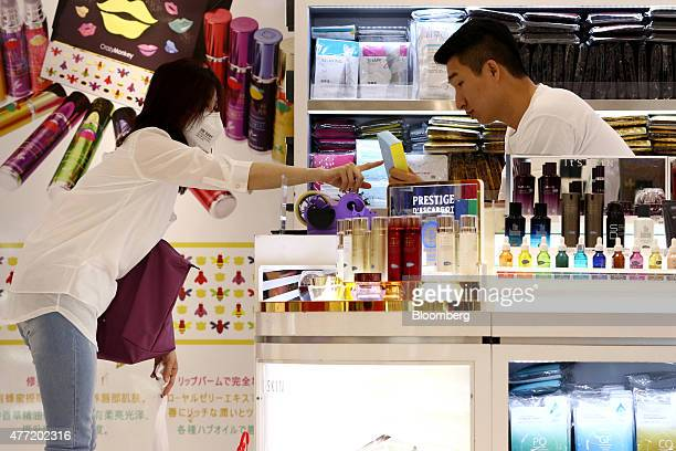 A customer wearing a mask points at the box of a cosmetic product at a Hotel Lotte Co Duty Free store in Seoul South Korea on Monday June 15 2015 As...