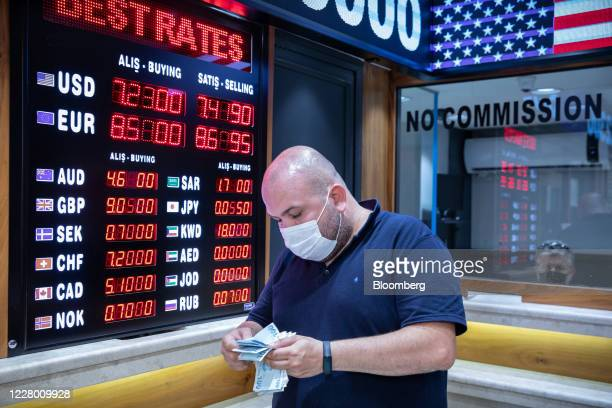 Customer wearing a protective face mask counts 100 Turkish lira banknotes at a foreign currency exchange bureau in Istanbul, Turkey, on Tuesday, Aug....