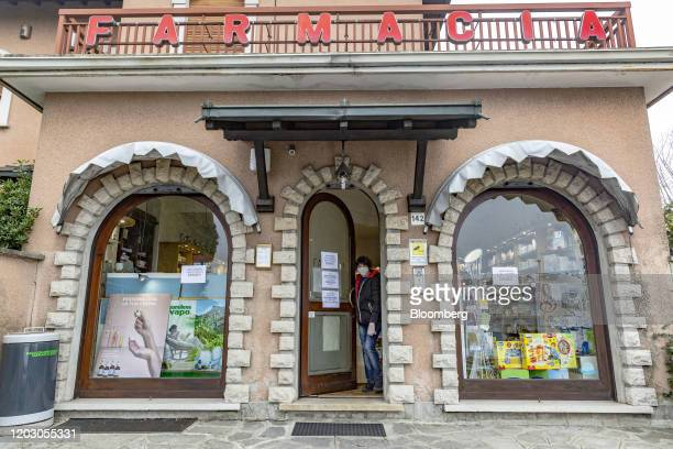 A customer wearing a protective face mask exits a pharmacy in a yellow quarantine zone near the quarantine red zone in the town of Codogno in...
